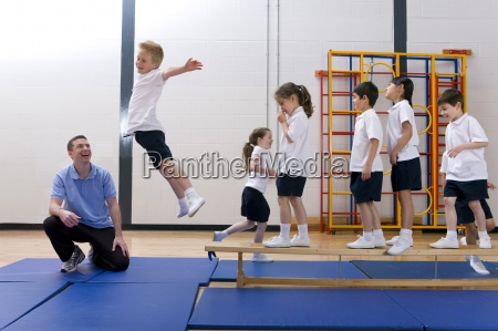 gym teacher watching school boy jump