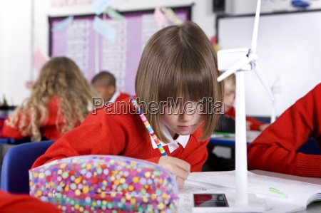 serious school girl writing in notebook