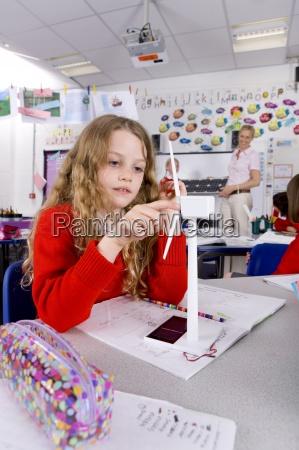 serious school girl spinning model wind
