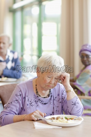 a senior woman having lunch looking