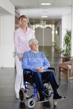 a care assistant pushing a senior