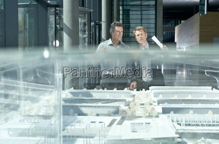 two businessmen discussing an architectural scale