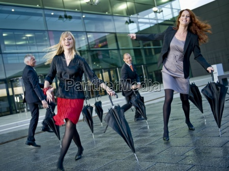 four businesspeople dancing outside a modern