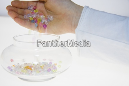 a person pouring colored beads into
