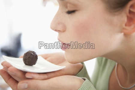 a woman smelling a chocolate on