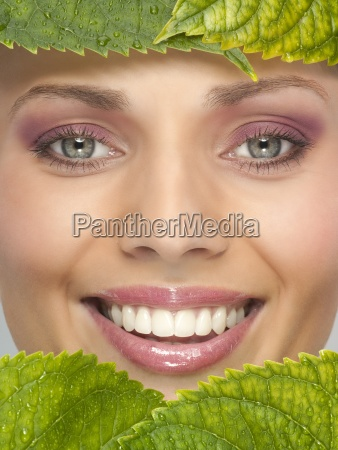 a womans face behind green leaves