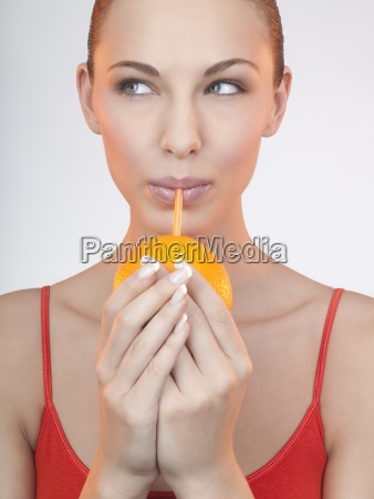 a woman drinking juice from an