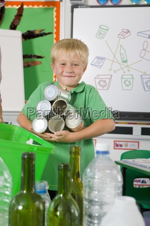 smiling student holding recyclable tin cans