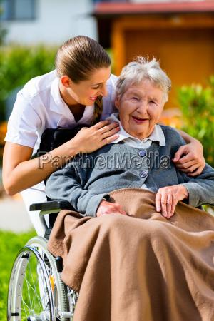 senior with carer in garden of