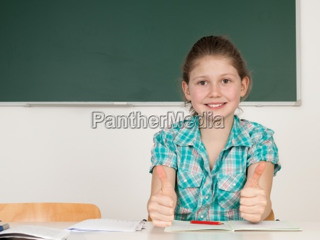 student in school holds up thumb