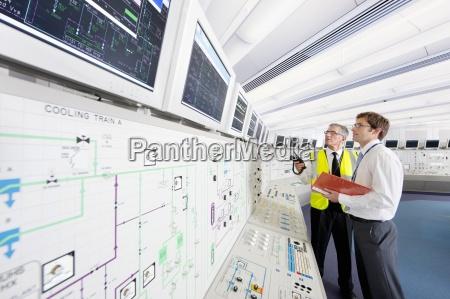 engineers looking up at computer monitors