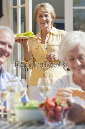 smiling senior woman serving grapes on