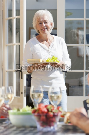 smiling senior woman serving grapes and