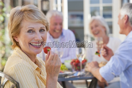 portrait of smiling senior woman eating