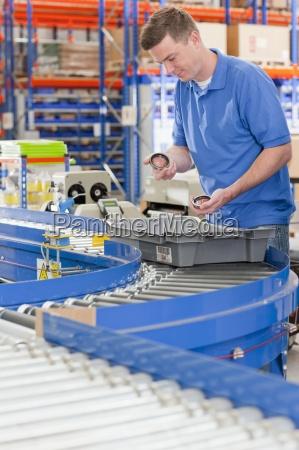 worker examining machine parts in bin