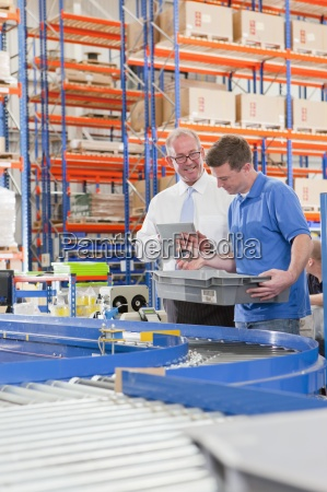 supervisor and worker examining machine parts