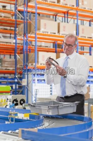 supervisor examining machine part in bin