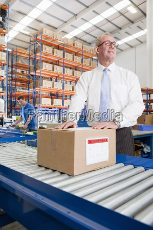 supervisor with cardboard box on production