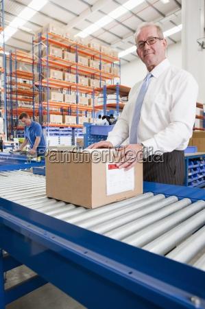 portrait of smiling supervisor with cardboard