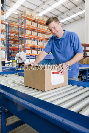 worker packaging cardboard box on production