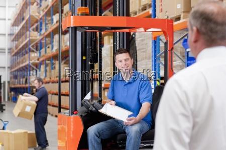 supervisor nearing worker in forklift in