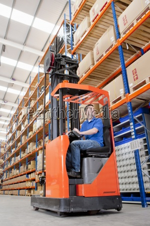 worker operating forklift in distribution warehouse