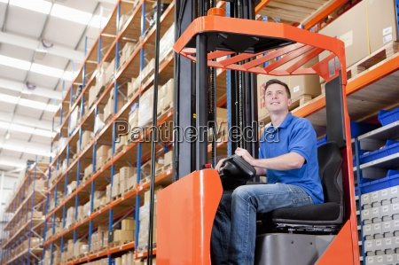 smiling worker operating forklift in distribution
