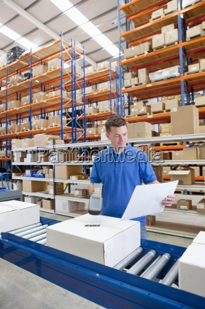smiling worker scanning box on production
