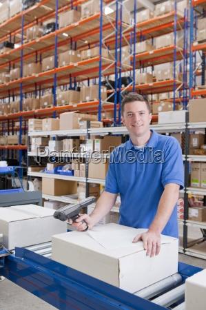 portrait of smiling worker scanning box