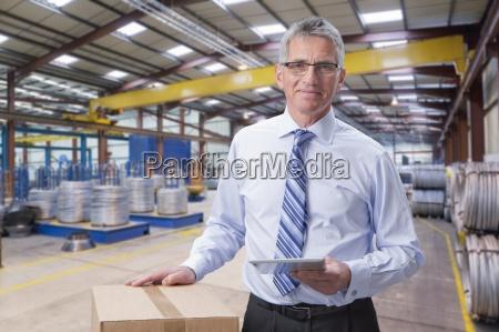 portrait of smiling supervisor holding digital