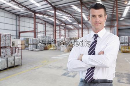 portrait of confident businessman in warehouse