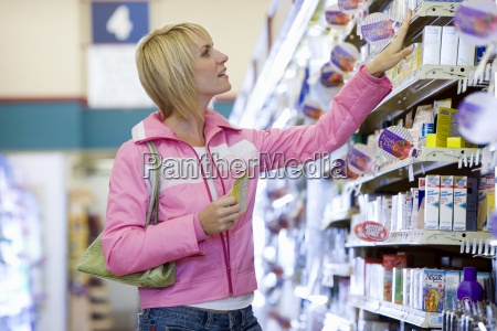 woman shopping in supermarket choosing item