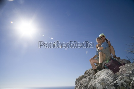 mature hikers sitting on clifftop edge