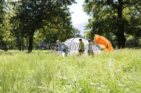 multi generational family setting up tent