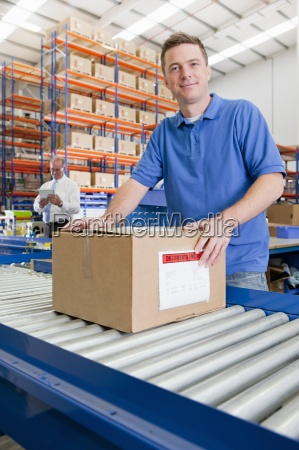 portrait, of, worker, with, cardboard, box - 12958654