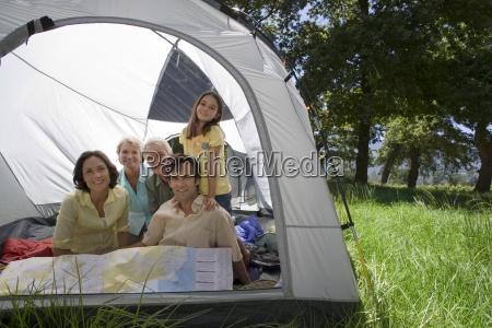 multi generational family relaxing inside tent