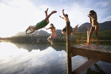 four young adults diving from jetty