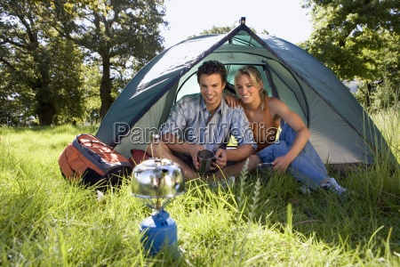 young couple sitting inside dome tent