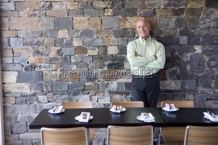 mature male restaurant owner standing beside