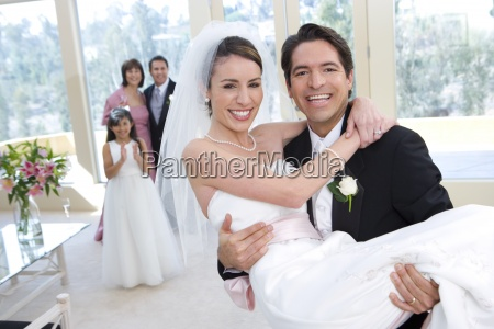 groom carrying bride in arms at