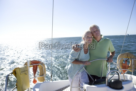 mature couple standing at helm of