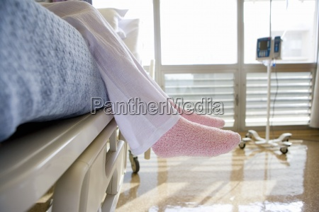 female patient wearing pink slippers sitting