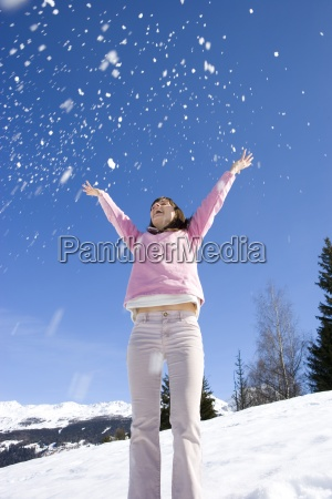 young woman throwing snow in air