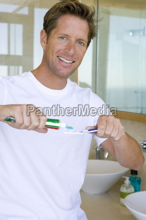 young man applying toothpaste on toothbrush