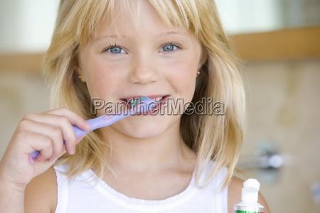 girl 6 8 brushing teeth in