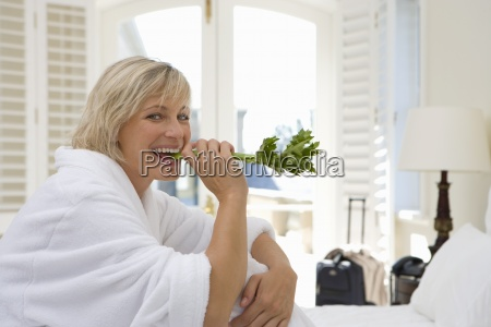 woman wearing white bath robe biting