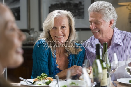 mature couple smiling at dinner table