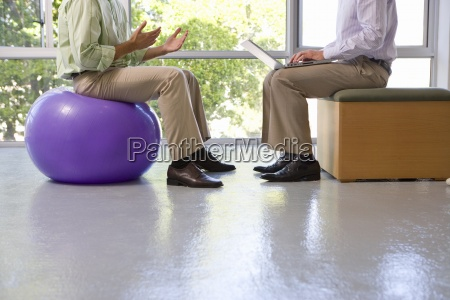businessman on exercise ball in meeting