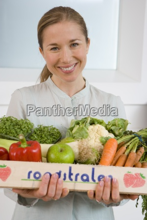 woman with box of vegetables smiling