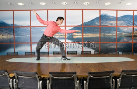 businessman pretending to surf on boardroom
